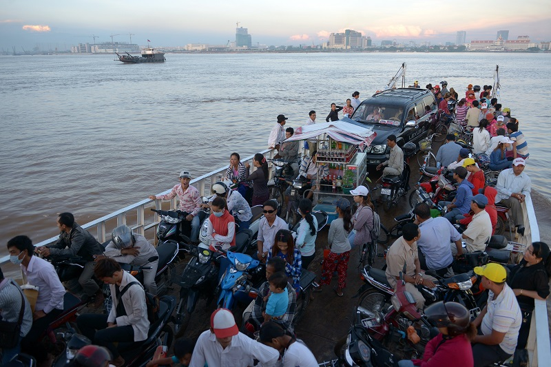 A ferry transports Cambodian people across the Mekong river in Phnom Penh on August 27, 2014. The Association of Southeast Asian Nations (ASEAN) has set 2015 as the target to create a single economic market across the 10-nation bloc that is home to some 600 million people. TANG CHHIN SOTHY/AFP/Getty Images.