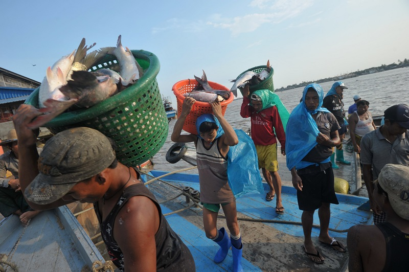Workers carry fish baskets as they unload a catch from a boat at a jetty near a fish market in Yangon on April 23, 2015. Soe Than WIN/AFP/Getty Images.