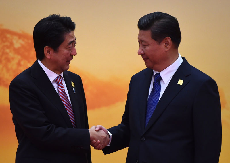 Japan's Prime Minister Shinzo Abe shakes hands with China's President Xi Jinping at the Asia-Pacific Economic Cooperation (APEC) leaders meeting at Yanqi Lake, north of Beijing, on November 11, 2014. GREG BAKER/AFP/Getty Images.