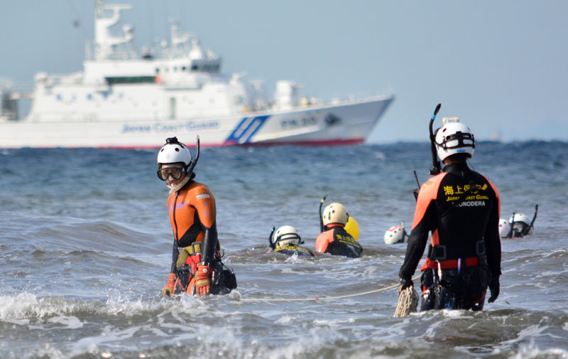 A Japanese Coast Guard marine rescue unit searches for typhoon victims off Oshima island, 120 km south of Tokyo on October 18, 2013. KAZUHIRO NOGI/AFP/Getty Images.