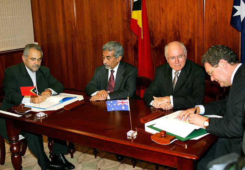 Australian Prime Minister John Howard and Timor-Leste Prime Minister Mari Alkatiri watch as their respective foreign ministers, Jose Ramos-Horta and Alexander Downer, sign the CMATS in Sydney, January 12, 2006. GREG WOOD/AFP/Getty Images.